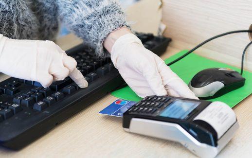 Mulher com luvas de borracha se protege contra coronavírus durante venda de cartão de crédito