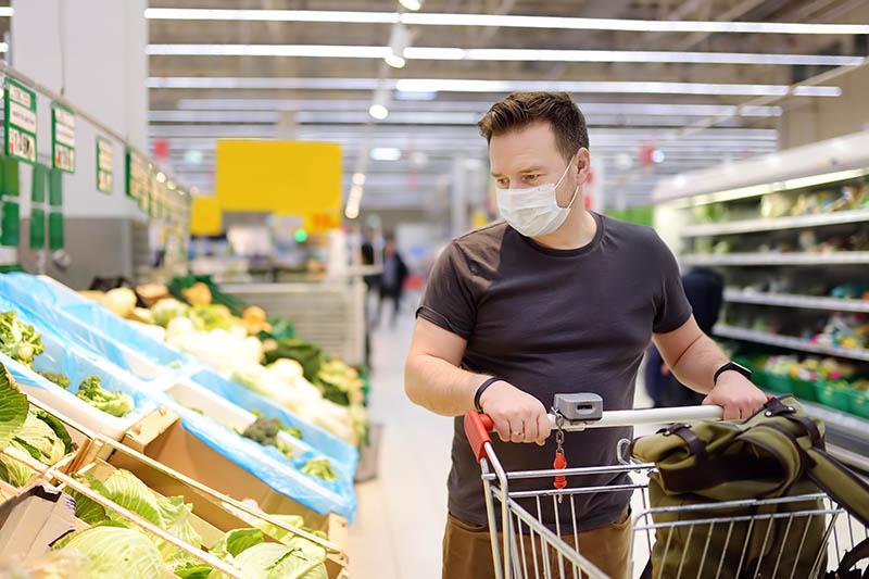 Homem faz compras em supermercado com máscara para se proteger da pandemia de coronavírus